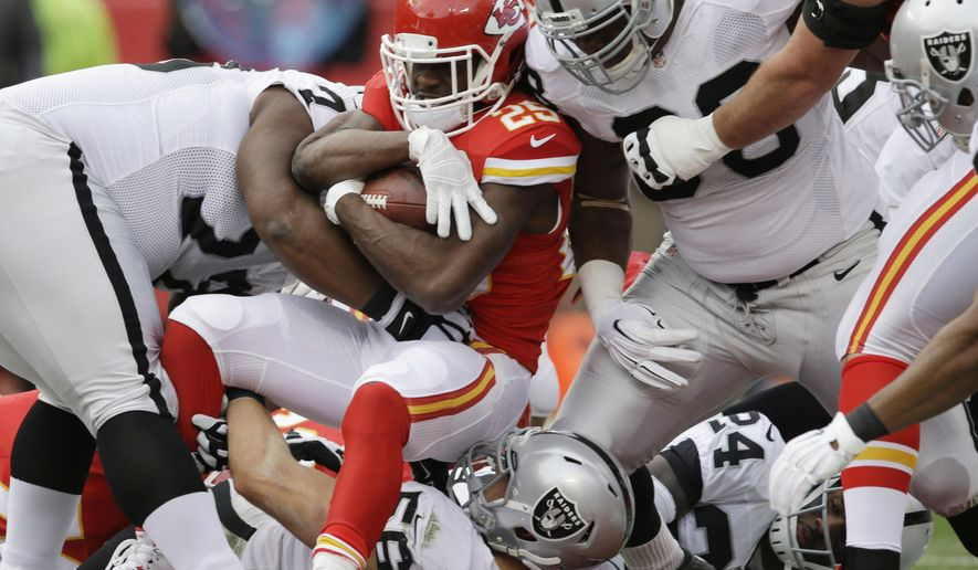 Kansas City Chiefs running back Jamaal Charles (25) is tackled by Oakland Raiders middle linebacker Miles Burris (56) and Oakland Raiders defensive end C.J. Wilson, right, during the first half of an NFL football game in Kansas City, Mo., Sunday, Dec. 14, 2014. (AP Photo/Orlin Wagner)