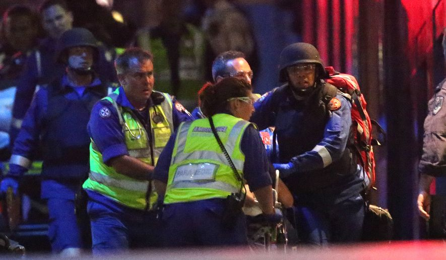 """Emergency personnel wheel an injured hostage to an ambulance during a cafe siege in the central business district of Sydney , Australia, Tuesday, Dec. 16, 2014.  A swarm of heavily armed police stormed the cafe in the heart of downtown Sydney early Tuesday, ending a siege where a gunman had been holding an unknown number of people hostage for more than 16 hours. A police spokesman confirmed """"the operation is over,"""" but would not release any further details about the fate of the gunman or his remaining captives. After a flurry of loud bangs, police swooped into the Lindt Chocolat Cafe shortly after five or six hostages were seen running from the building. (AP Photo/Rob Griffith)"""