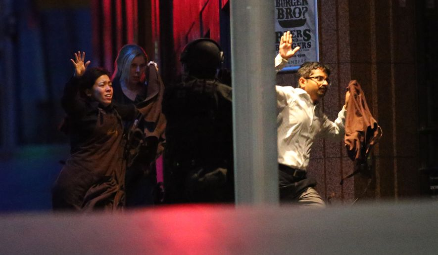 "Hostages run to safety  during a cafe siege in the central business district of Sydney , Australia, Tuesday, Dec. 16, 2014.  A swarm of heavily armed police stormed a cafe in the heart of downtown Sydney early Tuesday, ending a siege where a gunman had been holding an unknown number of people hostage for more than 16 hours. A police spokesman confirmed ""the operation is over,"" but would not release any further details about the fate of the gunman or his remaining captives. After a flurry of loud bangs, police swooped into the Lindt Chocolat Cafe shortly after five or six hostages were seen running from the building. (AP Photo/Rob Griffith)"
