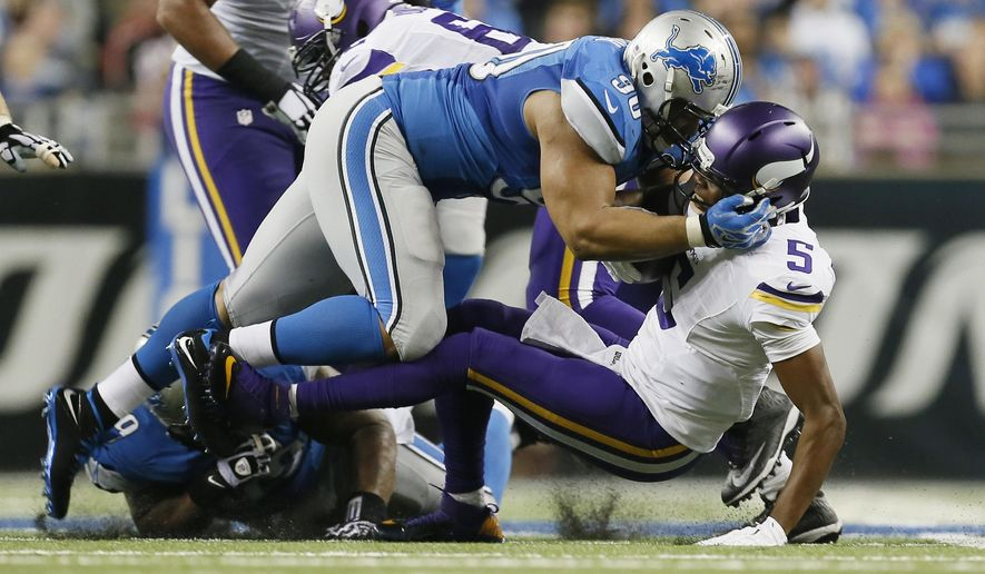 Detroit Lions defensive tackle Ndamukong Suh (90) sacks Minnesota Vikings quarterback Teddy Bridgewater (5) during the second half of an NFL football game at Ford Field in Detroit, Sunday, Dec. 14, 2014. (AP Photo/Paul Sancya)