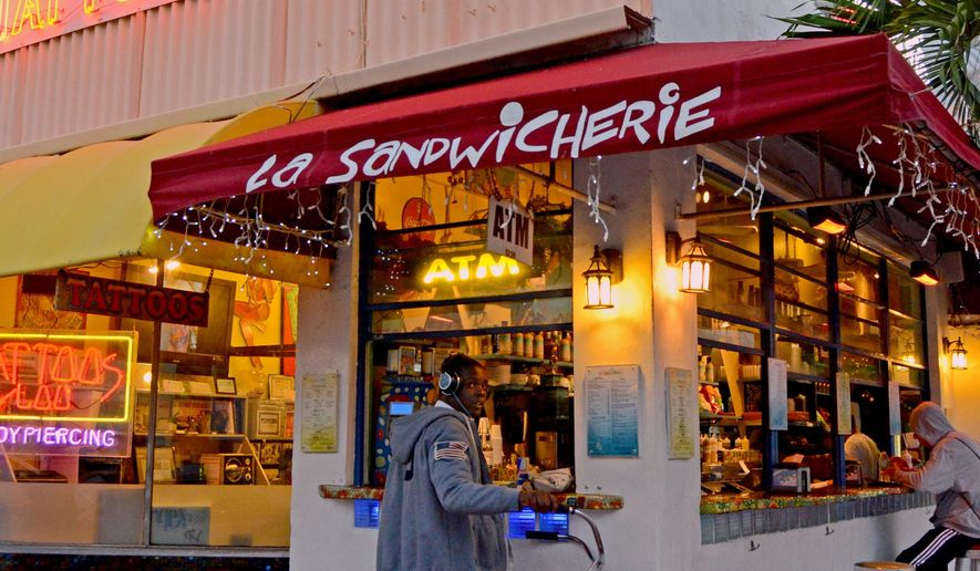 This Nov. 3, 2014 photo shows Roudolphe Douceur of Miami Beach waiting for his order at La Sandwicherie, in Miami Beach, Fla.,  a highlight of South Beach's side streets where travelers will find inexpensive local favorites for food, accommodations and souvenirs. (AP Photo/Jennifer Kay)