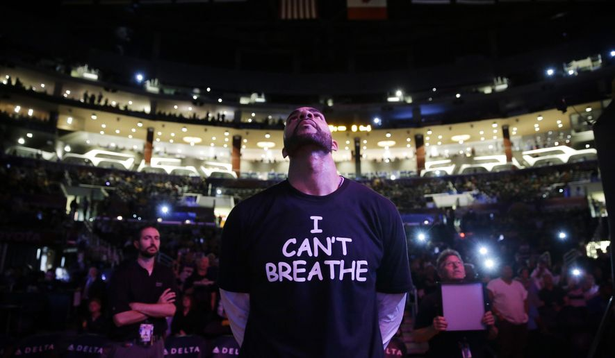"FILE - In this Dec. 9, 2014, file photo, Los Angeles Lakers' Carlos Boozer stands before team introductions for an NBA basketball game against the Sacramento Kings in Los Angeles. Dozens of athletes in recent weeks have responded to confrontations between authorities and black citizens in Ferguson, Mo., New York and elsewhere by wearing T-shirts bearing such statements as ""I Can't Breathe"" and ""Hands Up, Don't Shoot!"" (AP Photo/Jae C. Hong, File)"