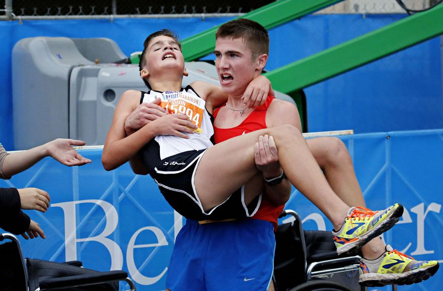 Trace Greer, right, carries his brother Judson Greer after they crossed the finish line together in the half marathon during the MetroPCS Dallas Marathon Sunday, Dec. 14, 2014 in Dallas, Texas. (AP Photo/The Dallas Morning News, G.J. McCarthy)