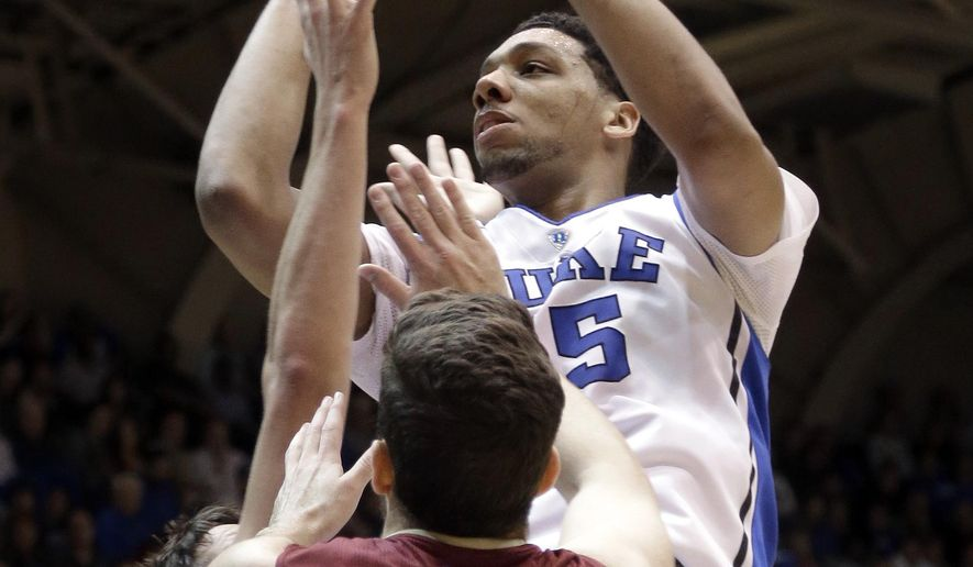 Duke's Jahlil Okafor shoots as Elon's Ryan Winters (32) defends during the first half of an NCAA college basketball game in Durham, N.C., Monday, Dec. 15, 2014. (AP Photo/Gerry Broome)