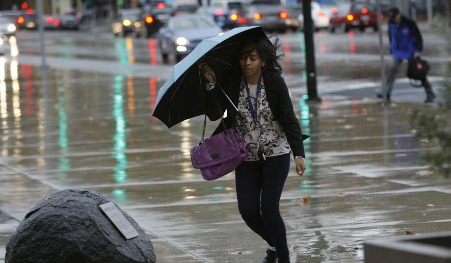 Farheen Sultana fights the wind and rain at Fifth and Santa Clara streets in San Jose, Calif., on Monday, Dec. 15, 2014. A new storm dumped more rain on already waterlogged parts of Northern California Monday, , causing minor road flooding, scattered power outages and airport delays. (AP Photo/San Jose Mercury News, Gary Reyes)  MAGS OUT; NO SALES