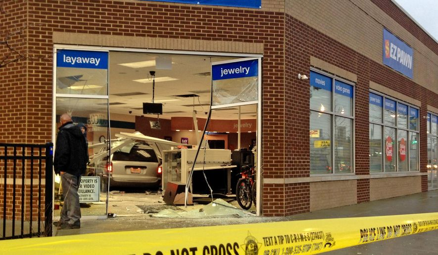 "In this Dec. 9, 2014 photo, yellow tape surrounds the scene where a van can be seen inside the glass entrance of a store on South Western Avenue, in Chicago. At least a dozen ""crash-and-grab"" burglaries, in which gangs drive stolen cars directly into retail businesses, has shop owners nervous and police stumped in Chicago and its surrounding suburbs. (AP Photo/Sun-Times Media, Brian Jackson)  MANDATORY CREDIT, MAGS OUT, NO SALES"