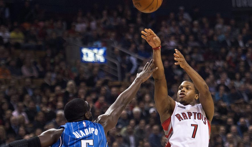 Toronto Raptors guard Kyle Lowry (7) makes a jump shot past Orlando Magic guard Victor Oladipo (5) during first half NBA basketball action in Toronto on Monday, Dec. 15, 2014. (AP Photo/The Canadian Press, Nathan Denette)