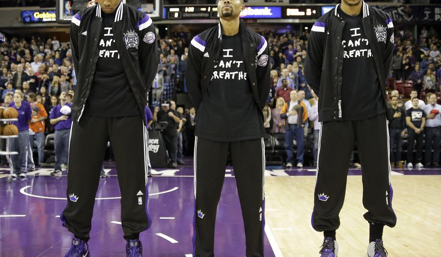 """FILE - In this Dec. 11, 2014, file photo, Sacramento Kings' Rudy Gay, left, Ramon Sessions, center, and Eric Moreland stand for the national anthem before an NBA basketball game against the Houston Rockets in Sacramento, Calif. Dozens of athletes in recent weeks have responded to confrontations between authorities and black citizens in Ferguson, Mo., New York and elsewhere by wearing T-shirts bearing such statements as """"I Can't Breathe"""" and """"Hands Up, Don't Shoot!"""" (AP Photo/Rich Pedroncelli, File)"""