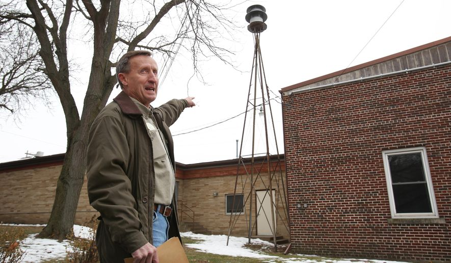 In this Thursday, December 11, 2014 photo, Gary Althoff, village president, attempts to talk over the sound of the noon siren going off in Bangor, Wis. The village siren in the small La Crosse County community has been sounding at least four times a day for decades. Now the 1,470 residents of Bangor will decide in a referendum if the village should silence the long-standing tradition. (AP Photo/Wisconsin State Journal, Amber Arnold)