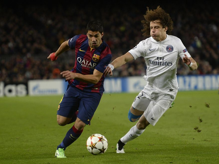 Barcelona's Luis Suarez, left, and PSG's David Luiz challenges for the ball during the Group F Champions League soccer match between FC Barcelona and PSG at the Camp Nou stadium in Barcelona, Spain, Wednesday Dec. 10, 2014. (AP Photo/Manu Fernandez)