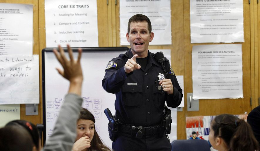 "FILE - In this Tuesday, Oct. 28, 2014 file photo, Officer Phil White of the San Jose Police Department teaches a ""Choices and Consequences"" class for 5th grade students at Christopher Elementary School in San Jose, Calif.  White is on leave as his department investigates comments posted online that threaten those protesting the recent deaths of unarmed black men in Ferguson, Missouri, and New York. In the tweets, White said he would kill anyone who threatens him or his family. He also said he would be off-duty at the movies with his gun if anyone ""feels they can't breathe or their lives matter."" (AP Photo/Bay Area News Group, Gary Reyes)"