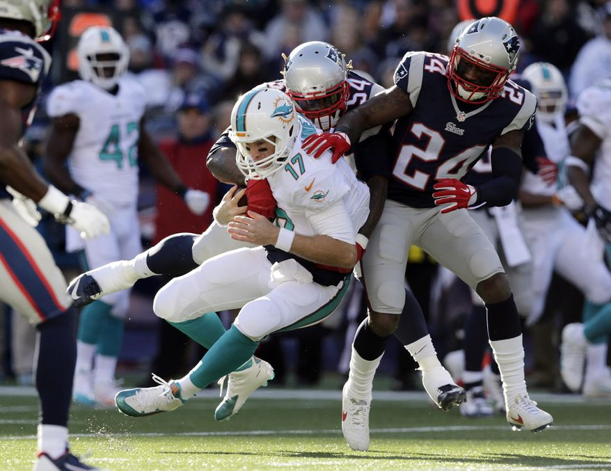 New England Patriots outside linebacker Dont'a Hightower, rear, tackles Miami Dolphins quarterback Ryan Tannehill (17) alongside Patriots cornerback Darrelle Revis (24) in the first half of an NFL football game Sunday, Dec. 14, 2014, in Foxborough, Mass. (AP Photo/Charles Krupa)