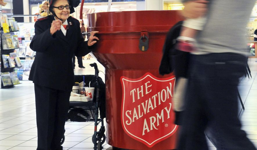 In this Nov. 15, 2014 photo, 92 year-old Salvation Army bell ringer Esther Rahenkamp, of Avon Park, Fla., greets shoppers at NorthPark Mall  in Davenport, Iowa, standing next to a 700-pound donation kettle. Since 2001, Rahenkamp has lived in central Florida but comes back to the Quad-Cities each year with the help of Maj. Gary Felton, a good friend and local Salvation Army coordinator, to take up her post as bell ringer -- often as much as eight hours per day, six days per week.  (AP Photo/The Dispatch, Gary Krambeck)  QUAD CITY TIMES OUT
