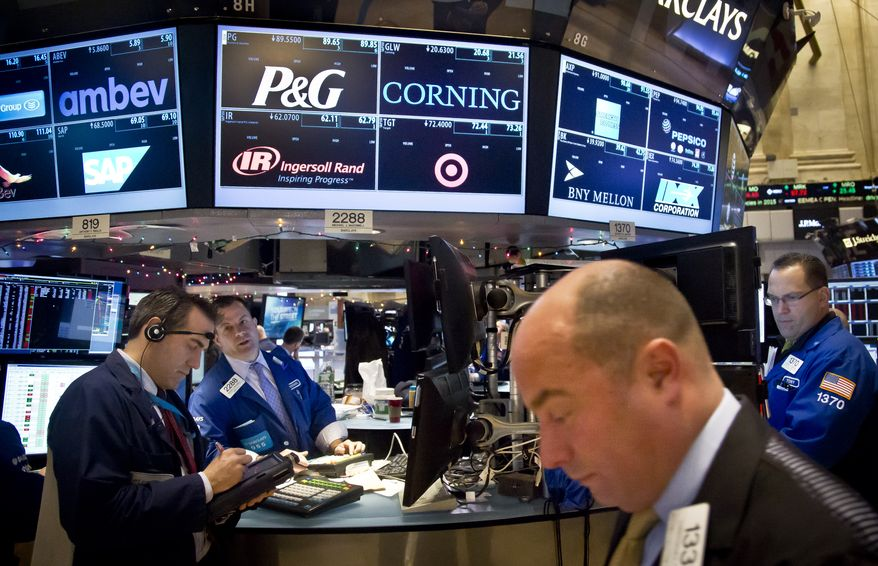 Traders confer as the review stock information at the New York Stock Exchange during early trading, Monday, Dec. 15, 2014, in New York. U.S. stocks opened broadly higher Monday following the biggest weekly losses in two and a half years. (AP Photo/Bebeto Matthews)