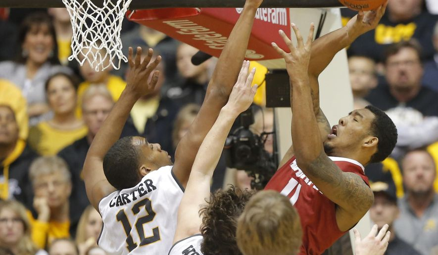 Wichita State's Darius Carter, left, Evan Wessel (3) and Ron Baker (31) try to block the shot of Alabama's Shannon Hale during the first half of the NCAA college basketball game in Wichita, Kan., on Tuesday, Dec. 16, 2014. (AP Photo/The Wichita Eagle, Travis Heying)