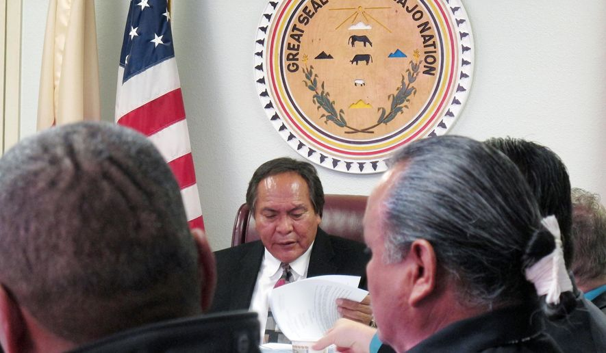 FILE - In this Oct. 9, 2014 file photo, Richie Nez, center, an administrative judge for the Navajo Nation, looks over documents at a hearing in Window Rock, Ariz. On Tuesday, Dec. 16, 2014, Nez, the Navajo Nation's chief hearing officer who disqualified a presidential candidate for not speaking Navajo fluently as required by tribal law, was fired. Tribal spokesman Deswood Tome says Nez was given the option to resign or be terminated for not having a state bar license. (AP Photo/Felicia Fonseca,File)