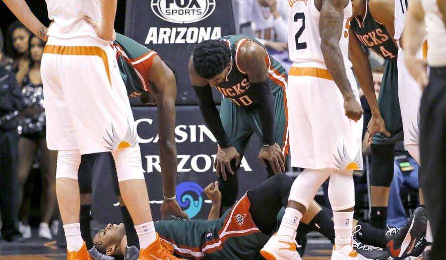In this Monday, Dec. 15, 2014, photo, Milwaukee Bucks' Jabari Parker lies on the court after injuring his knee during the second half of an NBA basketball game against the Phoenix Suns in Phoenix. (AP Photo/Matt York)