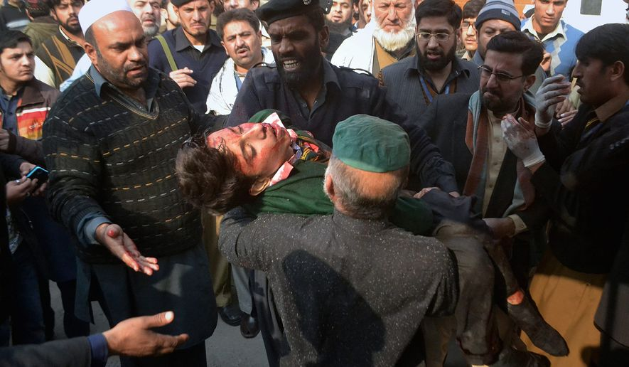 Young targets: Hospital security guards carried out the dead and wounded after the Taliban launched one of the most deadly terrorist attacks ever in Pakistan. Gunmen stormed an army-run school that teaches children in grades one through 10. (Associated Press)