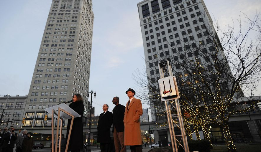 Stacy Fox addresses attendees of the lighting of facade of the David Whitney building in Detroit on Monday, Dec. 15, 2014. The Aloft Detroit hotel at the building is scheduled to open Thursday along with a restaurant and lounge. The building wasn't used for years and construction on the $92 million redevelopment began in 2013. (AP Photo/The Detroit News, Elizabeth Conley)