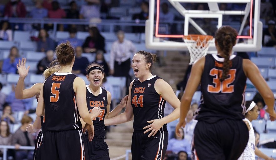 Oregon State's Ruth Hamblin (44), Samantha Siegner (5) and Sydney Wiese (24) celebrate as Deven Hunter (32) joins in the celebration following the team's win over North Carolina in an NCAA college basketball game in Chapel Hill, N.C., Tuesday, Dec. 16, 2014. Oregon State won 70-55. (AP Photo/Gerry Broome)