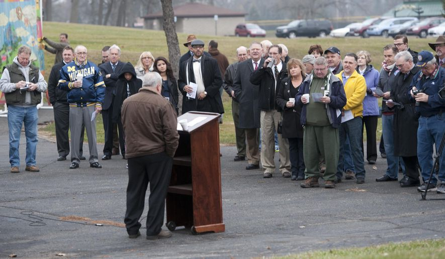 People attend a ceremony before the start  of the Cascade Falls wall demolition on Monday, Dec. 15, 2014. The demolition will take a couple of weeks to complete.  (AP Photo/The Jackson Citizen Patriot, J. Scott Park)