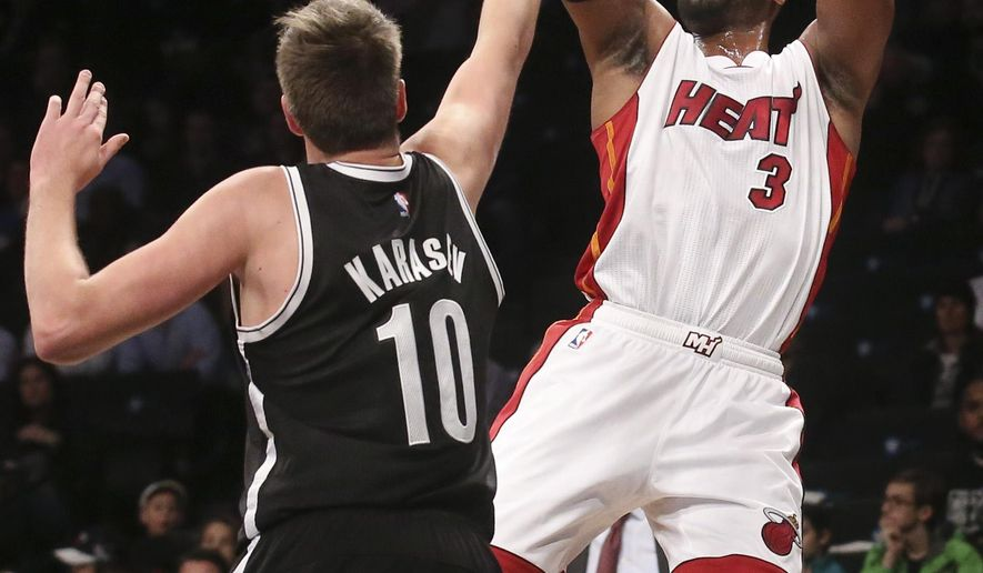 Miami Heat guard Dwyane Wade (3) shoots over Brooklyn Nets guard Sergey Karasev (10) in the first half their NBA basketball game at the Barclays Center, Tuesday, Dec. 16, 2014, in New York. (AP Photo/John Minchillo)
