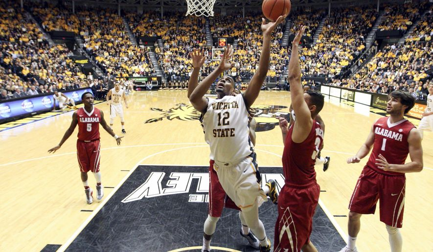 Wichita State's Darius Carter shoots in front of Alabama defenders during an NCAA college basketball game in Wichita, Kan., on Tuesday, Dec. 16, 2014. (AP Photo/The Wichita Eagle, Travis Heying)