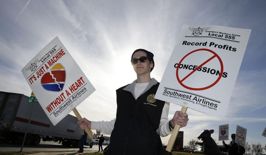 Cameron Cerf  holds a protest sign with Southwest Airlines employees at the entrance to Love Field in Dallas, Tuesday, Dec. 16, 2014. Saying Southwest Airlines is neglecting workers and its customers, baggage handlers are bringing attention to the company's slide in on-time performance as they seek a new contract after three years of negotiations. (AP Photo/LM Otero)