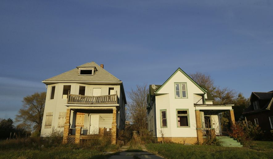 FILE--In this Nov. 7, 2014 file photo, sunlight falls on two adjacent abandoned homes in west Detroit. The state of Michigan has divided more than $75 million in federal funding to fight blight among 12 cities, with Detroit getting about two-thirds of the money. The funding details announced Tuesday, Dec. 16, 2014 are part of the latest in a series of efforts to deal with vacant and dilapidated buildings across the state. (AP Photo/Carlos Osorio)