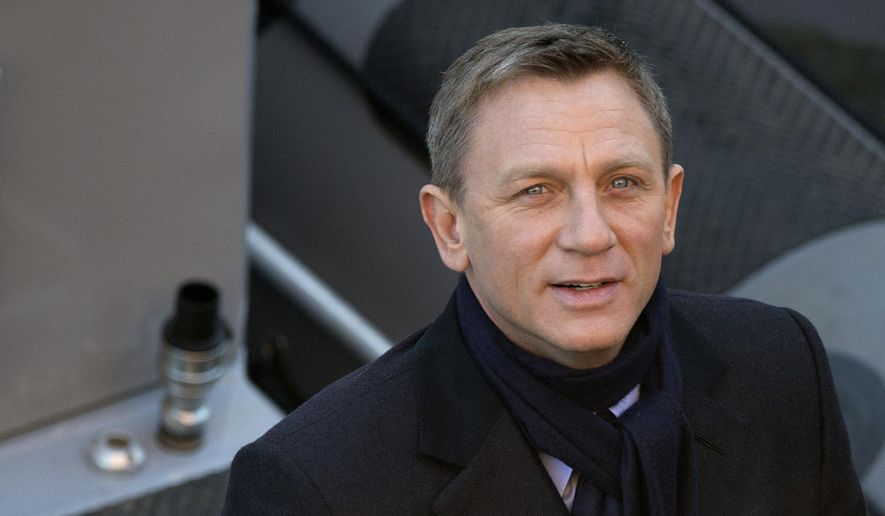 Actors Daniel Craig smiles for photographers as he films a scene for the new James Bond film, Spectre, in London, Tuesday, Dec. 16, 2014. (AP Photo/Alastair Grant)