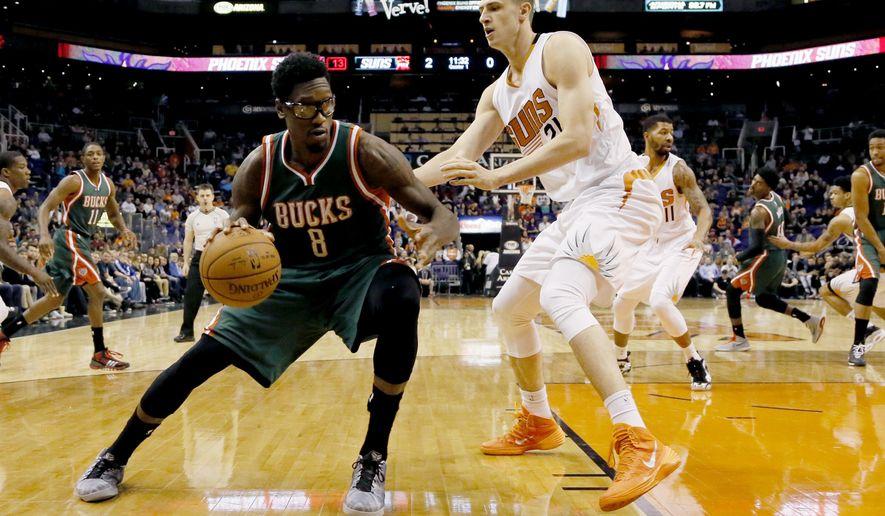 Milwaukee Bucks' Larry Sanders (8) dribbles near Phoenix Suns' Alex Len during the first half of an NBA basketball game, Monday, Dec. 15, 2014, in Phoenix. (AP Photo/Matt York)