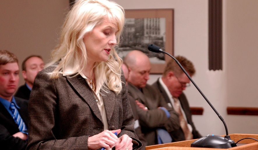 FILE - In this Thursday, Jan. 24, 2013 file photo, Corrections Department Director Leann Bertsch reads testimony to the House Appropriations Committee in Bismarck, N.D., on a plan to move a minimum security facility to the state penitentiary. A proposal by North Dakota's top prison administrator to have counties share in state penitentiary costs if a quota is exceeded is meeting opposition from local officials, law enforcement, judges and prosecutors. Bertsch will ask the Legislature when it meets next month to set a county-by-county allocation at state prison facilities using a formula based on the population of each county. (AP Photo/James MacPherson, File)