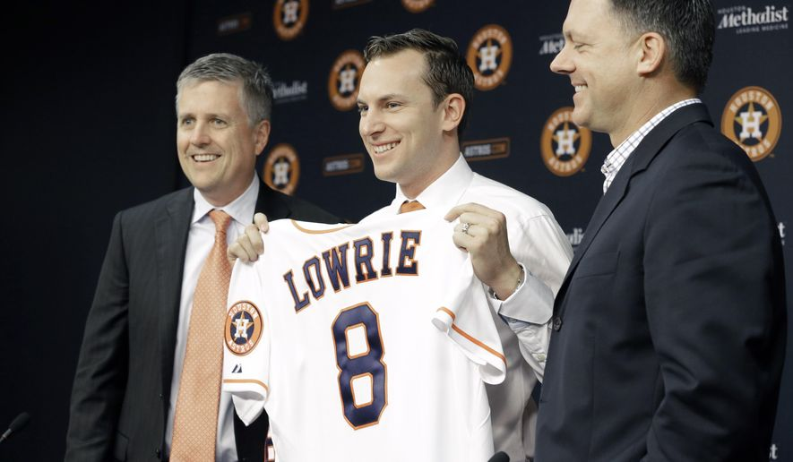 New Houston Astros shortstop Jed Lowrie, center, stands between General Manager Jeff Luhnow, left, and Manager A.J. Hinch as he holds up his new jersey at a press conference Tuesday, Dec. 16, 2014, in Houston. Lowrie is returning to the Astros after two seasons in Oakland. (AP Photo/Pat Sullivan)