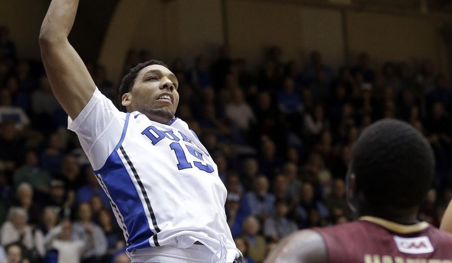 Duke's Jahlil Okafor (15) dunks as Elon's Austin Hamilton (10) looks on during the second half of an NCAA college basketball game in Durham, N.C., Monday, Dec. 15, 2014. Duke won 75-62. (AP Photo/Gerry Broome)