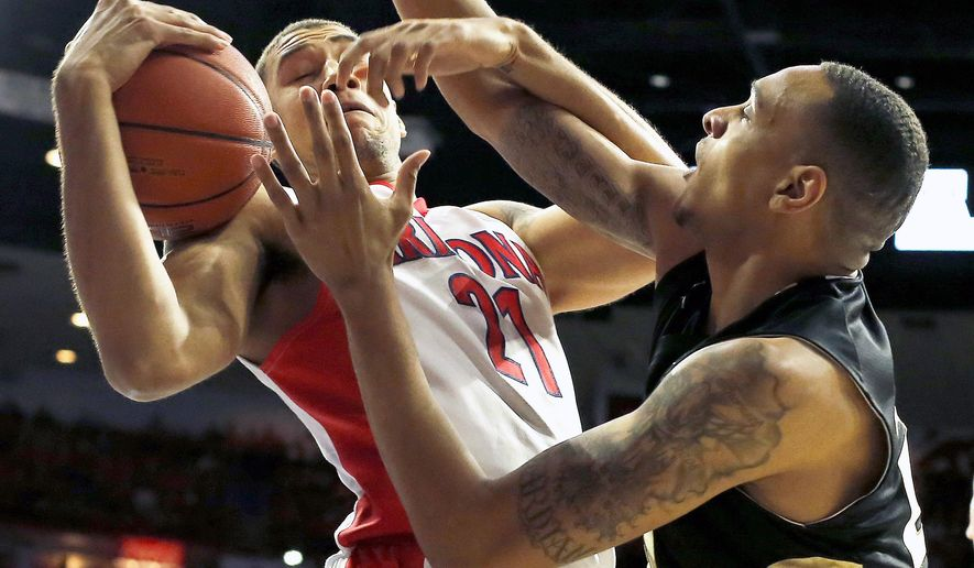Arizona forward Brandon Ashley (21), left, an Oakland forward Tommie McCune (23) battle for the ball during the first half of an NCAA college basketball game, Tuesday, Dec. 16, 2014, in Tucson, Ariz. (AP Photo/Rick Scuteri)