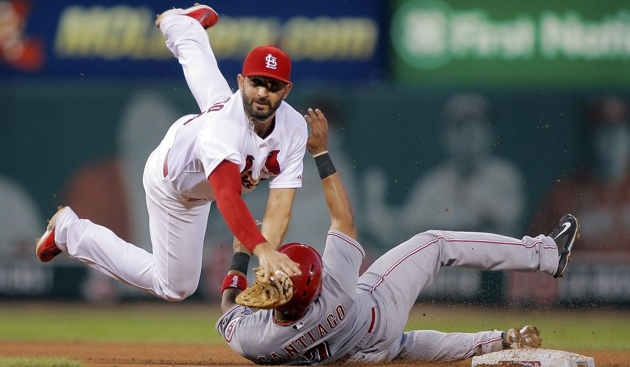 FILE - In this Aug. 20, 2014, file photo, St. Louis Cardinals second baseman Daniel Descalso, left, is unable to turn a double play after making an out against Cincinnati Reds' Ramon Santiago during the fifth inning of a baseball game in St. Louis' Zack Cozart was safe at first. The Colorado Rockies needed a versatile infielder, and so they added Descalso with a $3.6 million, two-year contract Tuesday, Dec. 16. (AP Photo/Scott Kane, File)