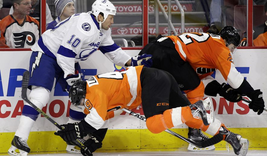 Philadelphia Flyers' Scott Laughton (49) is knocked down by Tampa Bay Lightning's Brenden Morrow (10) past Luke Schenn (22) during the first period of an NHL hockey game, Tuesday, Dec. 16, 2014, in Philadelphia. (AP Photo/Matt Slocum)