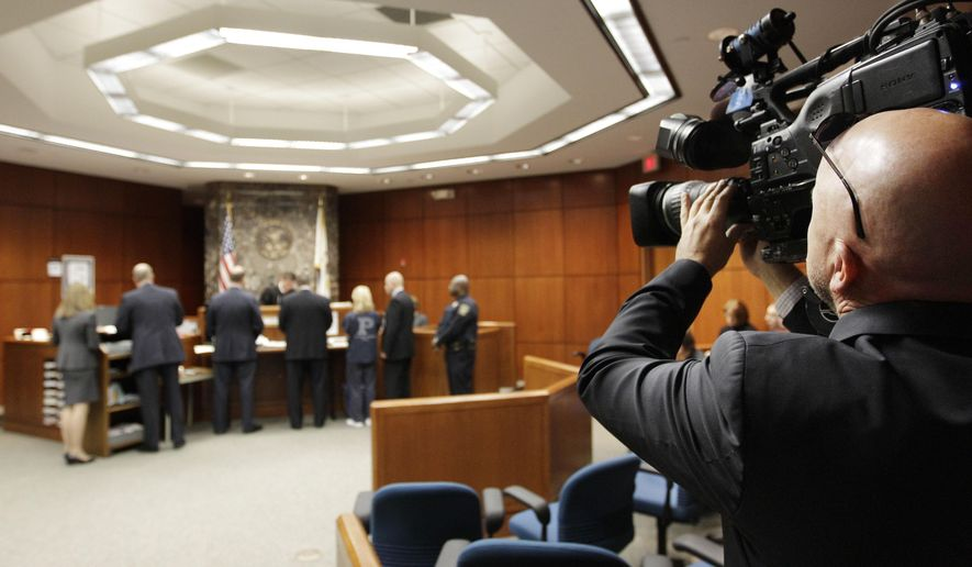 FILE - In this Nov. 21, 2011 file photo, Sean Maroney of WGN TV operates a pool television camera during a hearing before DuPage County Judge Robert Kleeman in Wheaton, Ill. Illinois Supreme Court Chief Justice Rita Garman and Cook County Chief Judge Timothy Evans announced Tuesday, Dec. 16, 2014 that the  Supreme Court has allowed the use of cameras and audio recording devices in Cook County courts on an experimental basis starting next month. Cook County is the largest and latest of dozens of counties in Illinois that have joined a state high court camera pilot program that launched in 2012. (AP Photo/M. Spencer Green, Pool, File)