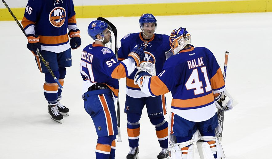 New York Islanders defenseman Matt Donovan (46) skates to celebrate the team's 3-2 win over the Chicago Blackhawks with center Frans Nielsen (51), defenseman Lubomir Visnovsky (11) and goalie Jaroslav Halak (41) in an NHL hockey game on Saturday, Dec. 13, 2014, in Uniondale, N.Y. (AP Photo/Kathy Kmonicek)