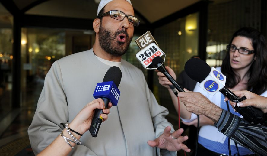 In this April 18, 2011, file photo, Man Haron Monis speaks to the media as he leaves the Downing Centre in Sydney after a pre-trial hearing where he is accused of sending offending letters to the families of soldiers killed in Afghanistan. Monis, the gunman in the 16-hour-long siege at the Lindt Cafe in downtown Sydney, was killed Tuesday, Dec. 16, 2014, in a police operation to rescue the people he was holding hostage. (AP Photo/AAP Image, Dean Lewins)