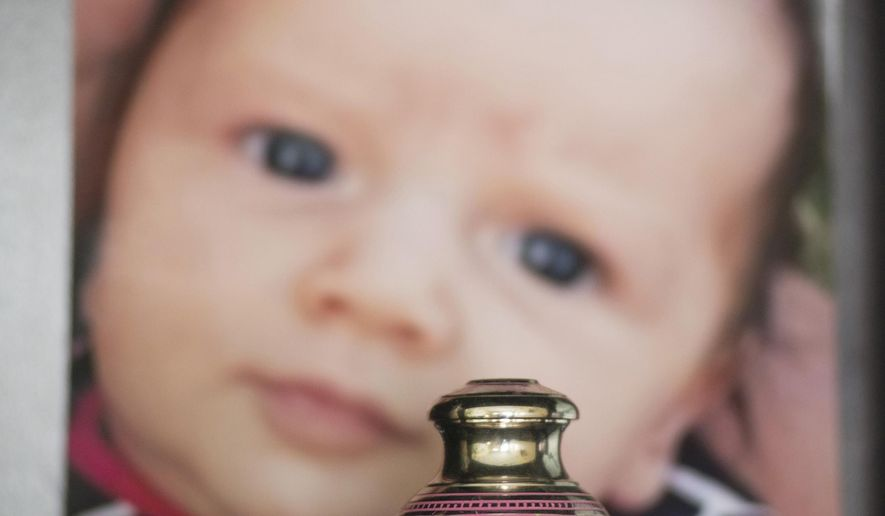ADVANCE FOR USE THURSDAY, DEC. 18, 2014, AT 12:01 A.M. EST AND THEREAFTER- In this Nov. 13, 2014, photo, a small urn containing the ashes of Mattisyn Blaz is displayed on a bookshelf in front of a photo of the infant girl in the home of Jennifer Blaz, 34, in Butte, Mont. At least 760 children died of abuse or neglect in the U.S. in a six-year span in plain view of child protection authorities, The Associated Press has found, including the death of 2-month-old Mattisyn. (AP Photo/Lido Vizzutti)