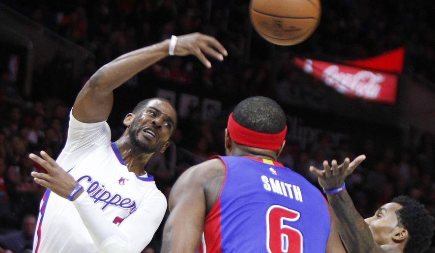 Los Angeles Clippers guard Chris Paul, left, passes the ball above Detroit Pistons forward Josh Smith (6) and guard Brandon Jennings, right, in the first half of an NBA basketball game in Los Angeles, Monday, Dec. 15, 2014. (AP Photo/Alex Gallardo)