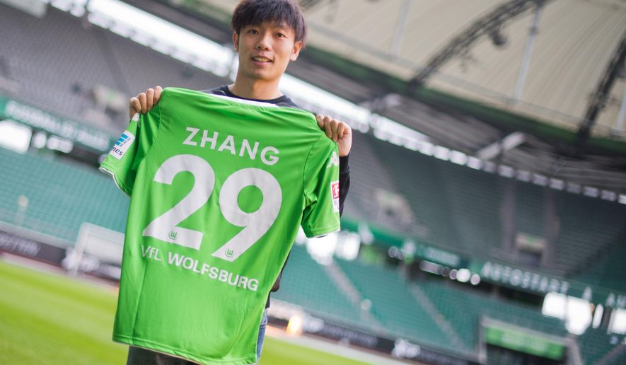 The new player for German first division soccer club of VfL Wolfsburg, Zhang Xizhe from China,  poses in the stadium in Wolfsburg, Germany, Tuesday Dec. 16, 2014.   (AP Photo/dpa, Julian Stratenschulte)