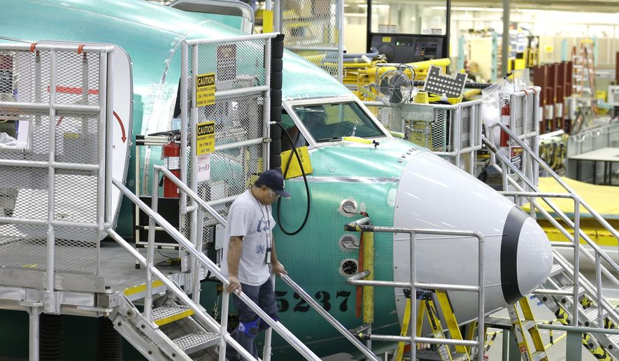 A worker walks down stairs next to the nose of a Boeing 737-800 airplane being assembled Tuesday, Dec. 16, 2014, at Boeing's 737 facility in Renton, Wash. Boeing and Puget Sound Energy announced Tuesday that Boeing plans to switch to using all-renewable energy at the factory, by buying more wind power credits and continuing to use hydropower. (AP Photo/Ted S. Warren)