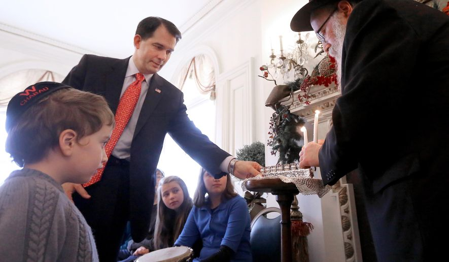 Wisconsin Governor Scott Walker assists Rabbi Yona Matusof of Madison, Wis. during a Menorah lighting ceremony as Shlomo Mutusof, 4, looks on during an observance at the Governor's Mansion in Madison Tuesday, Dec. 16, 2014. (AP Photo/Wisconsin State Journal, John Hart)