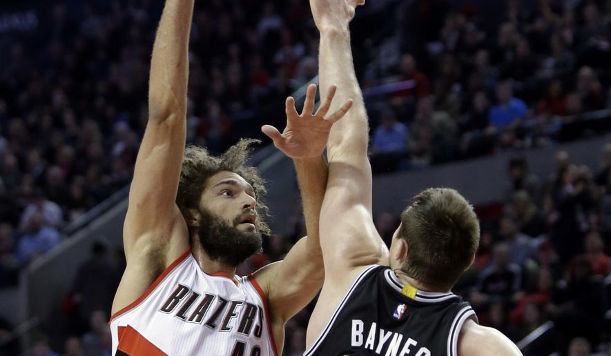 Portland Trail Blazers center Robin Lopez, left, shoots over San Antonio Spurs forward Aron Baynes, from Australia, during the first half of an NBA basketball game in Portland, Ore., Monday, Dec. 15, 2014.(AP Photo/Don Ryan)