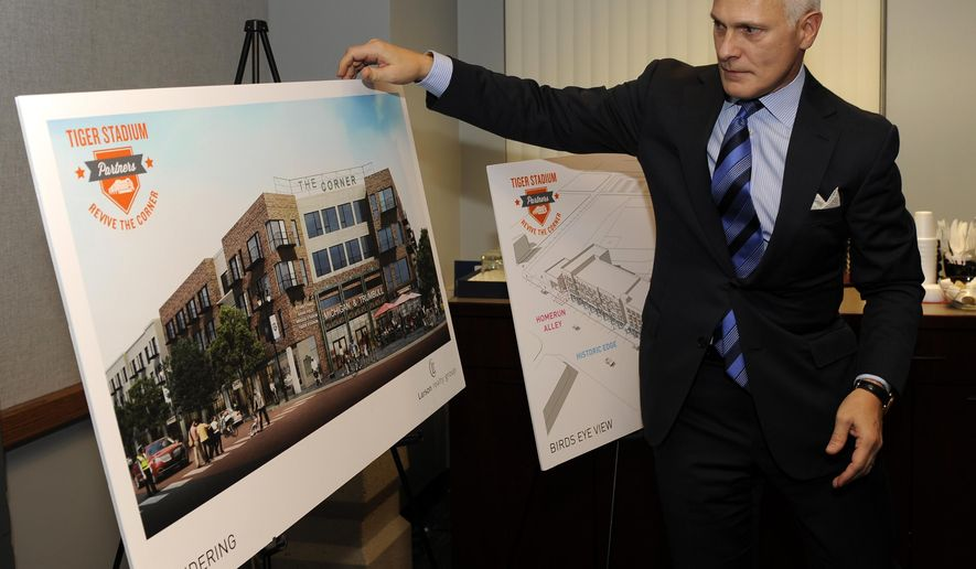 Eric Larson, President and CEO of Larson Realty Group, looks over a rendering of the former Tiger Stadium site during a news conference, Tuesday, Dec. 16, 2014, in Detroit. Officials with the city's Economic Development Corporation announce the Larson Realty Group as their recommended developer of the site at the former baseball stadium. (AP Photo/Detroit News, David Coates) DETROIT FREE PRESS OUT, HUFFINGTON POST OUT, MAGS OUT, MANDATORY CREDIT
