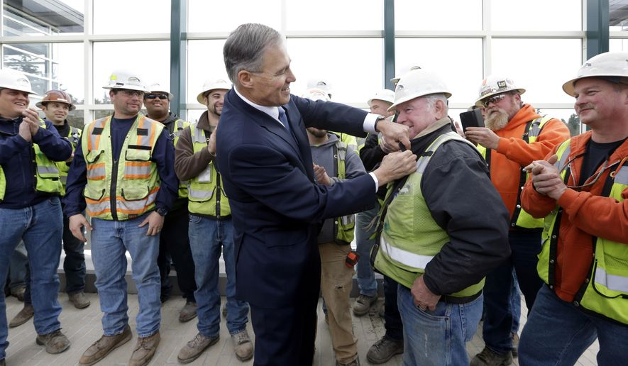 Gov. Jay Inslee, center, attaches an apple-shaped pin to the vest of construction worker Clem Massine after Inslee asked who was the hardest worker and Massine's colleagues called him out following a news conference Tuesday, Dec. 16, 2014, in Medina, Wash. Inslee, speaking from a spot overlooking the new floating bridge under construction on Lake Washington, announced his 12-year, $12 billion plan for rebuilding the state's transportation infrastructure. He said a third of the cost will be covered by a new tax on carbon pollution. The governor expects the state to collect $400 million a year from the state's worst polluters. Other expected sources of income for transportation include nearly $4 billion in tolls and other fees, plus more than $3 billion in construction bonds. (AP Photo/Elaine Thompson)