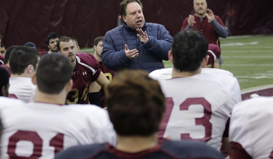 New York Yankees executive Mark Holtzman, director of non-baseball events, applauds as he addresses Boston College players following a football practice in Boston, Tuesday, Dec. 16, 2014. Boston College will face Penn State in the Pinstripe Bowl on Dec. 27th at Yankee Stadium.  At rear is Boston College head coach Steve Addazio. (AP Photo/Charles Krupa)