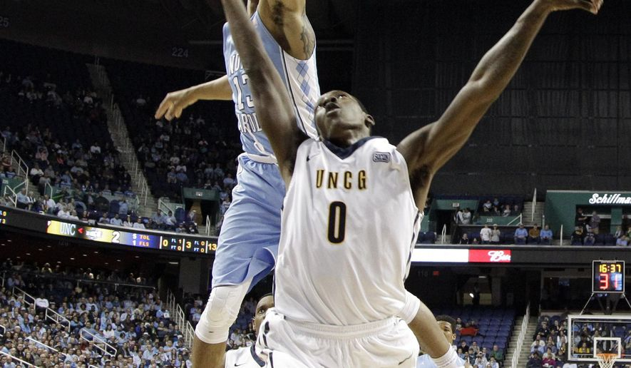 UNC Greensboro's Tevon Saddler, front, has his shot blocked by North Carolina's J.P. Tokoto, back, during the first half of an NCAA college basketball game in Greensboro, N.C., Tuesday, Dec. 16, 2014. (AP Photo/Chuck Burton)